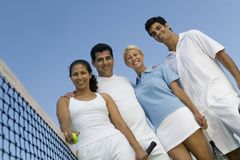Four mixed doubles tennis players at net on tennis court portrait low angle view Stock Photo