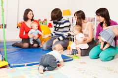 Group of mothers with their babies. Four moms with their lovely children in kindergarten Royalty Free Stock Image