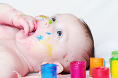 Four-months baby with multi-colored paints Stock Photography