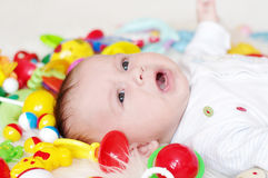 Four-months crying baby among toys Royalty Free Stock Image