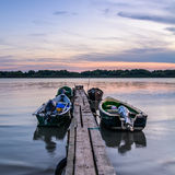 Four moored boats at sunset near a wooden pier. Vertical view of Royalty Free Stock Image