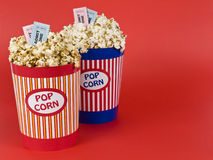 Four for the movies. Two popcorn buckets over a red background. Movie stubs sitting over the popcorn Royalty Free Stock Photo