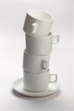 Four mugs stacked on saucer Royalty Free Stock Images