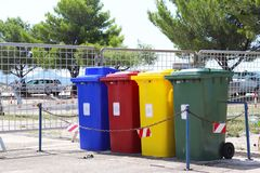 Four multicolored boxes for sorted garbage: red, green, blue and yellow. Recycling garbage in the tourist area. Infrastructure of. The Mediterranean marina stock images