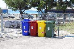 Four multicolored boxes for sorted garbage: red, green, blue and yellow. Recycling garbage in the tourist area. Infrastructure of. The Mediterranean marina stock image