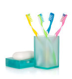 Four multicolored toothbrushes and soap Royalty Free Stock Photo