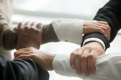 Four multiracial business people holding each others wrists, clo. Four multiracial business people holding each others wrists, diverse partners join hands Royalty Free Stock Photos