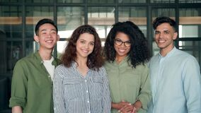 Four multiracial business startup coworkers standing in contemporary office.