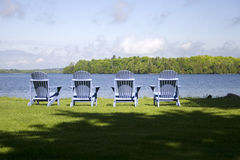 Four muskoka chairs. By a lake Royalty Free Stock Photography