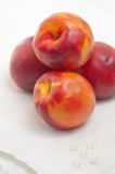 Four Nectarines and Embroidered Napkin Stock Photo