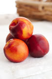 Four Nectarines and Embroidered Napkin Royalty Free Stock Photography
