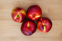 Four Nectarines on wooden table Royalty Free Stock Photos