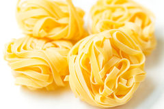 Four nests of dry pasta tagliatelle on tablecloth. Nests of dry pasta tagliatelle on white table cloth stock photos