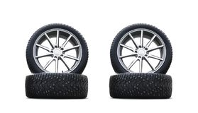 Four new good-looking snow tires isolated on the white background. A set of studded winter car tires. A set of wheels and tyre pac. Kages. Winter wheel parts royalty free stock photo