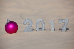 Four New Year`s figures are in the sand on the beach or seaside, cast a large shadow on the ground. Near the sand is pink ball. New Year Celebration and royalty free stock image