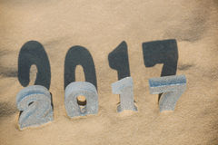 Four New Year's figures are in the sand on the beach or seaside, cast a large shadow on the ground. Stock Image