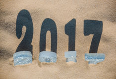 Four New Year's figures are in the sand on the beach or seaside, Royalty Free Stock Photo
