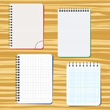 Four notebooks on a wooden table. Vector illustration Stock Images