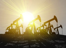 Four oil wells silhouetted against sunset Royalty Free Stock Photo