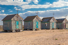 Four old beach huts Stock Images