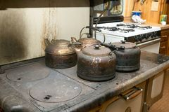 Four old blackened metal kettles on a stove Stock Images