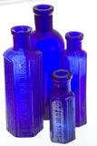 Four old blue glass medicine bottles. With ribbed design desiganating the contents as for external use only royalty free stock photos