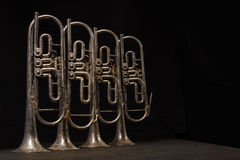 Four old brass wind instrument stand on a table Stock Photos