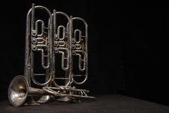 Four old brass wind instrument stand on a table Stock Images