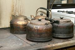 Old kettles standing on stove. Four old dirty rusty kettles standing on stove Stock Photos