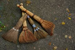 A set of old brooms lie on a gray road with leaves Stock Photos