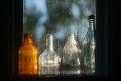 Old fashioned glass bottles. Four old fashioned glass bottles, back lit at sunset in a small window royalty free stock photo