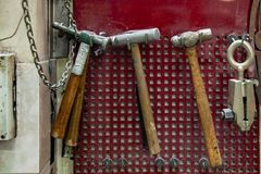 Four old hammers with a brown wooden handle and a clamp hang on the wall in the workshop for carpentry work on a red background royalty free stock photography