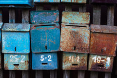 Four old mailboxes. With rust attached to the fence stock images