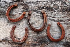 Four old rusty horseshoes on wooden ground. Horseshoe as lucky charm Stock Photo