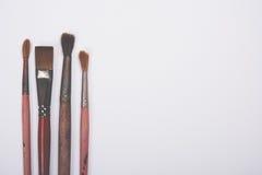 Four old used paintbrushes on white background Stock Image