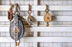 Old pulleys on a white wooden wall. Four old vintage pulleys hanging on a white painted wood wall Stock Images