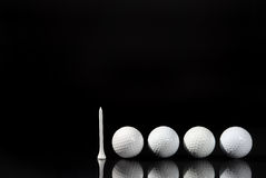 Four and One. Image of four golf balls and a tee with reflection Stock Photos