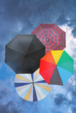 Four open umbrellas with blue rainy clouds Royalty Free Stock Image
