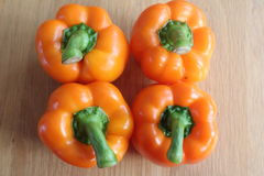 Four orange bell peppers Stock Image