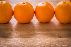 Four orange fruits organized in row on wooden Stock Images