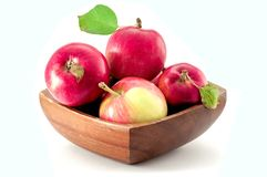Organic mottled red apples in a brown wooden bowl isolated on white background. Four organic mottled red apples in a wooden bowl isolated on white background royalty free stock photography