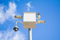 Four outside security cameras cover multiple angles on blue sky. Four outside security cameras cover multiple angles Stock Image