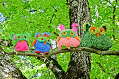 Four owls on the tree. An artistic composition of four owls on a trunk of a tree, puppets are handmade with wool and cotton stock photo