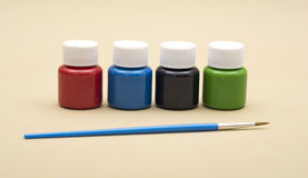 Four paint bottles in prime colors with painting brush Stock Images