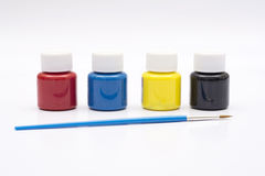Four paint bottles in prime colors with painting brush Royalty Free Stock Photo