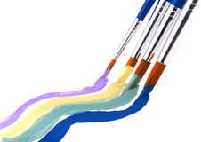 Four paint brushes with pleasing pastel color paint Royalty Free Stock Photos