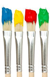 Four paintbrushes with color paints Stock Photos