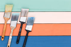 Four paintbrushes over painted wood surface Royalty Free Stock Images
