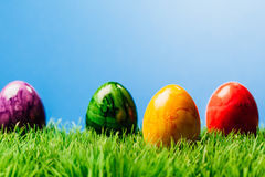Four painted easter eggs in grass, blue background. Four different color painted easter eggs in grass, blue background Royalty Free Stock Photo