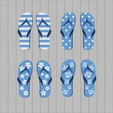 Four pair of different flip flops - blue white colors on grey wooden background stock illustration